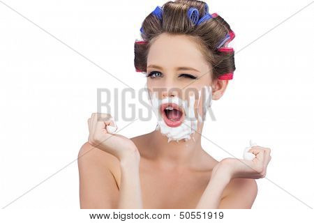 Cheeky young model in hair curlers posing with shaving foam on white background