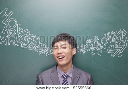 Portrait of young businessman in front of black board with Chinese and English script