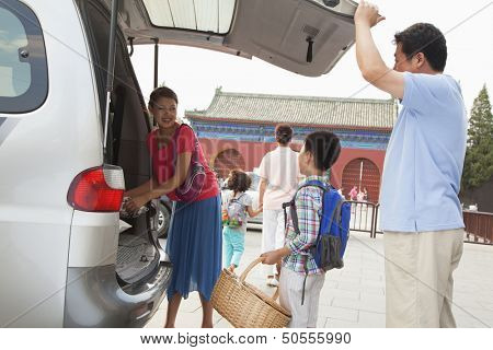 Family taking stuff out from the car, preparing for picnic