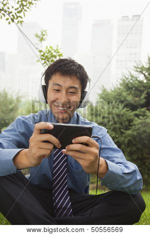 Young businessman listening to music on his MP4 player