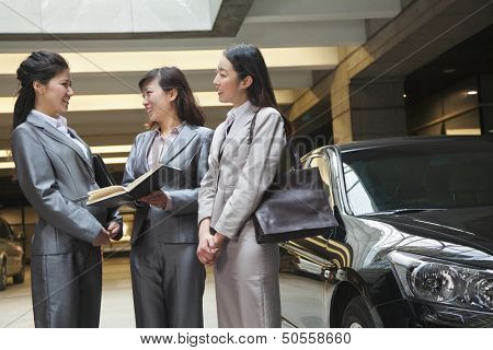 Three young businesswomen meeting and talking in parking garage