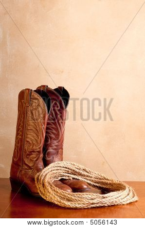 A Vertical Image Of A Pair Of Brown Cowboy Boots And A Coil Of Rope On A Wooded Surface With An Old