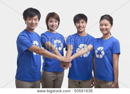 Four young people in recycling t-shirts with hands together, studio shot