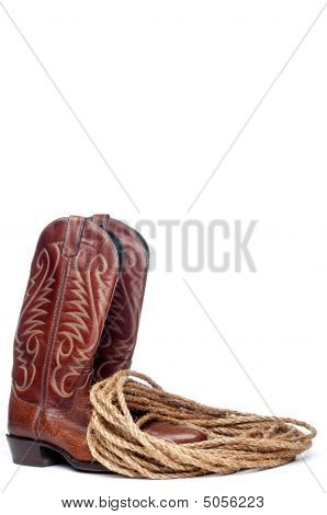 A Pair Of Brown Cowboy Boots And Rope