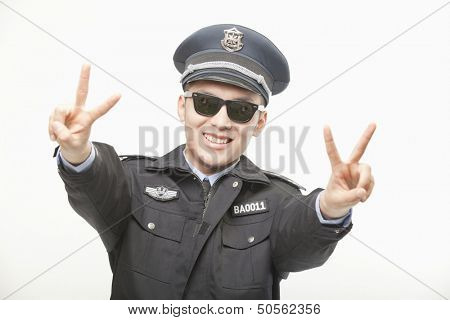 Police Officer Giving Peace Sign, Studio Shot