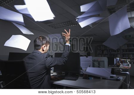 White-collar worker throwing white sheets in air in office