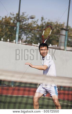 Adult men playing tennis