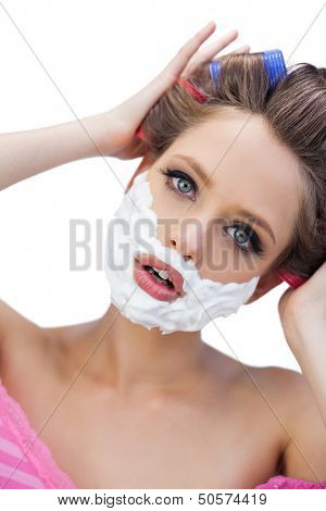 Curious model in hair curlers with shaving foam on white background