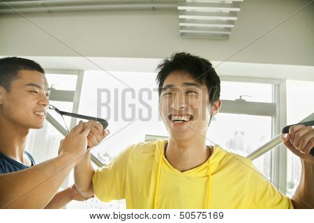 Young man exercising with his personal trainer in the gym