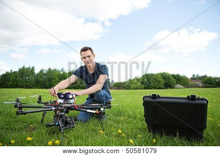 Portrait of young technician assembling octocopter drone crouching in park poster
