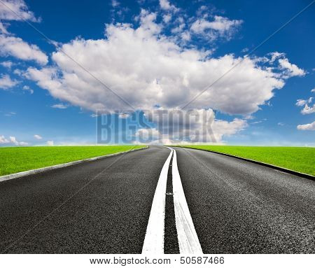 asphalt road through the green field and clouds on blue sky