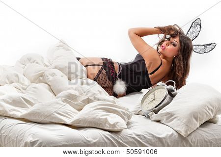 Close up of rabbit lying in bed. Woman - rabbit with alarm clock