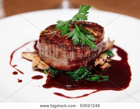 Tenderloin steak wrapped in bacon with red sauce and spinach