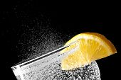 Sparkling water detail with an orange slice isolated on black background poster