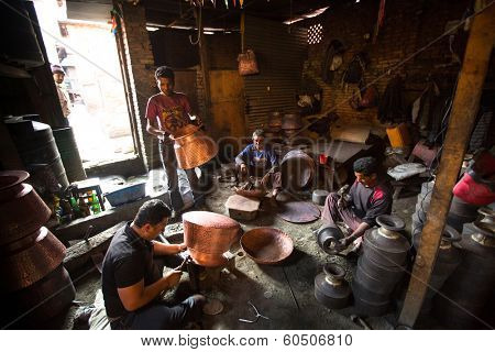 BHAKTAPUR, NEPAL - DEC 5, 2013: Unidentified Nepalese tinmans working in the his workshop. More 100 cultural groups have created an image Bhaktapur as Capital of Nepal Arts.