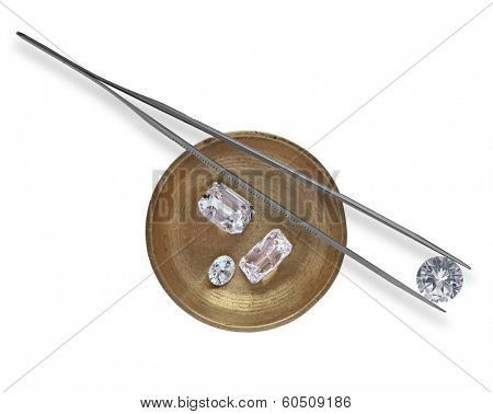 various cut cluster of diamonds in a working  brass tray and in tweezers