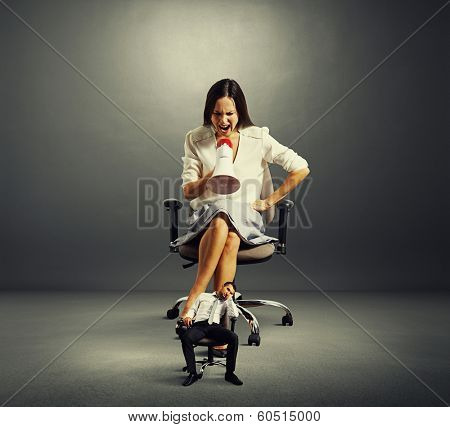 businesswoman screaming at tired small businessman over dark background