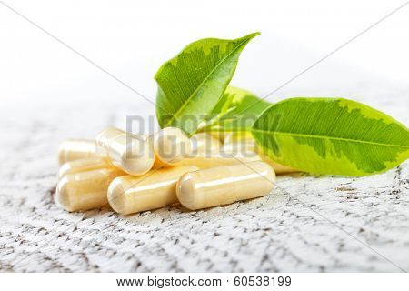 Capsules on white wooden background.
