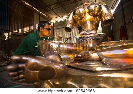 BHAKTAPUR, NEPAL - DEC 5, 2013: Unidentified Nepalese tinman working in the his workshop. More 100 cultural groups have created an image Bhaktapur as Capital of Nepal Arts.