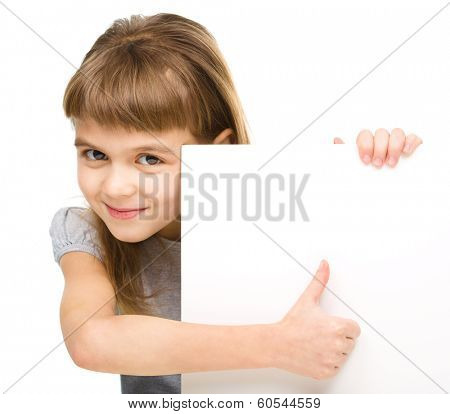 Little girl is looking out from the blank banner and showing thumb up sign, isolated over white