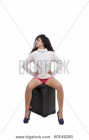 Seductive young female fashion model sitting on a speaker