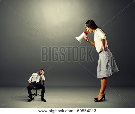 angry young woman screaming at small lazy man