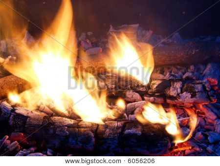 Flames in a fire pit with glowing embers poster