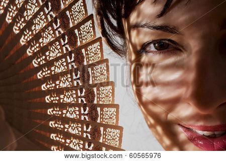 Beautiful Woman In Shadow With A Traditional Fan