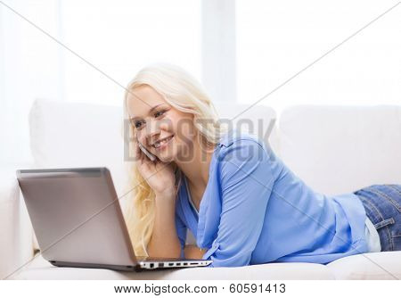 home, technology and internet concept - smiling woman with smartphone and laptop computer sitting on couch at home