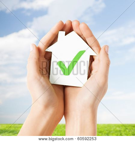 real estate and family home concept - hands holding paper house with green check mark