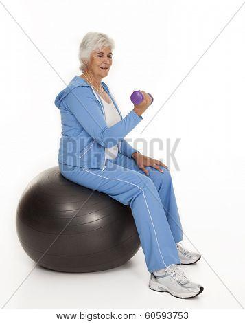 Female senior citizen seated on exercise ball lifting dumbbell on white background.