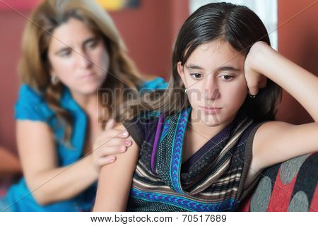 Sad teenage girl being comforted by her mother
