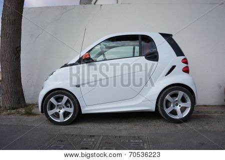 VALENCIA, SPAIN - AUGUST 20, 2014: A Smart Car parked in the street in Valencia, Spain.  The Smart Car is a small stylish city car with company headquarters in Germany, and the factory in France.