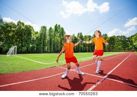 Running girl with baton hands it to other runner