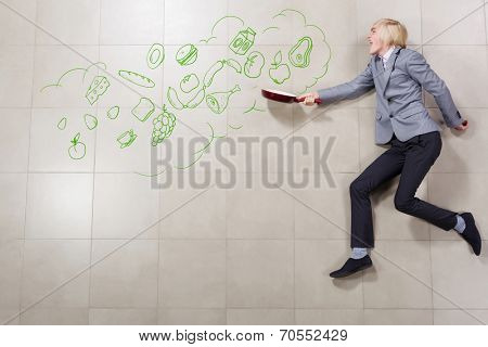 Young funny businessman running with pan in hand