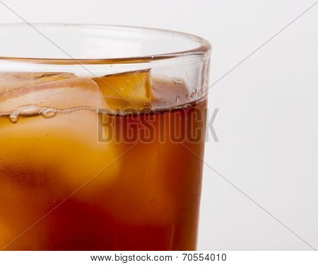 glass with ice tea full with ice cubes