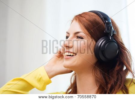 technology, music and happiness concept - smiling teenage girl in headphones at home