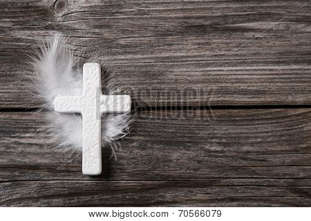 White Cross With Feather On An Old Rustic Background.
