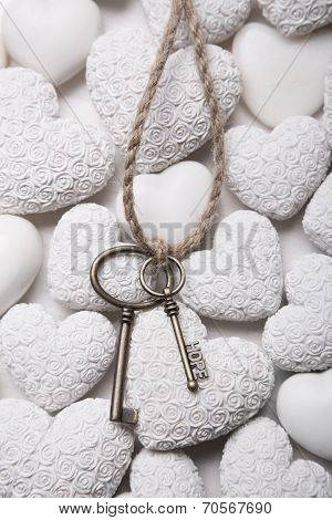 Mourning Or Hope Concept - Keys On A White Background Of Stone Hearts.
