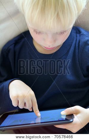 Young Child Playing Internet Game On Computer Tablet