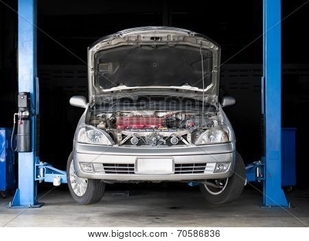 Car front hood opened elevated ready to be serviced poster