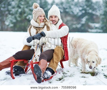 Happy couple sledding with toboggan and dog in winter