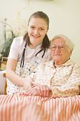 A young doctor / nurse visiting an elderly sick woman holding her hands with caring attitude. poster