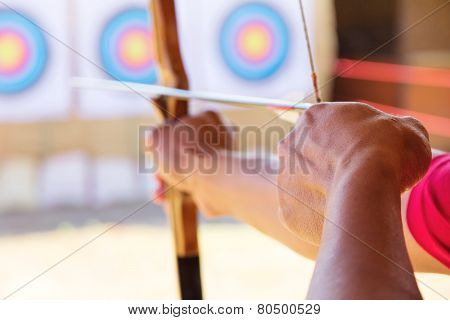Archer holds his bow aiming at a target