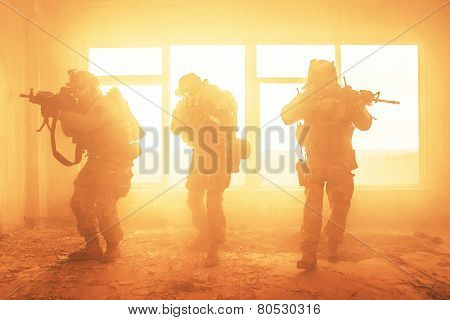 United States Army rangers during the military operation in the smoke and fire poster