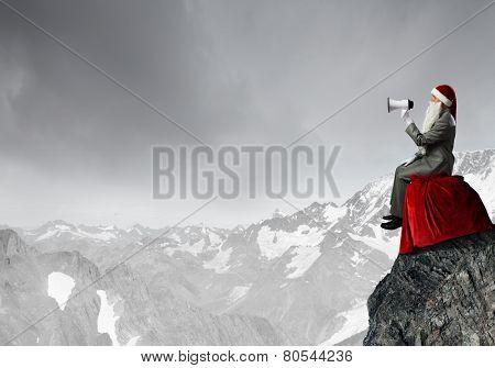 Businessman in Santa costume shouting in megaphone