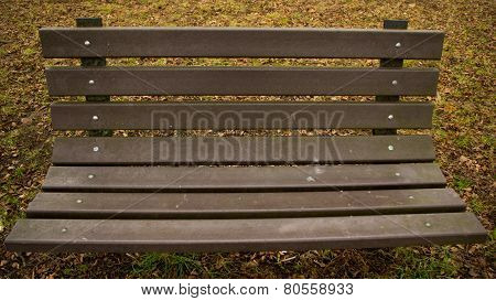 Wooden park bench in colour with grass in the background