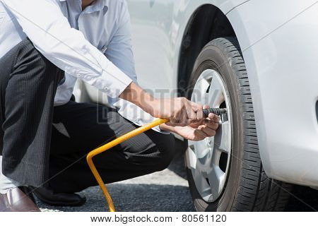 Asian driver checking air pressure and filling air in the tires of his car.