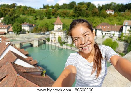 Travel selfie by woman in Bern Switzerland. Happy smiling multiracial Asian Caucasian girl taking self portrait photograph sitting on Nydeggbrucke by Aare river in the Swiss city of Bern. poster