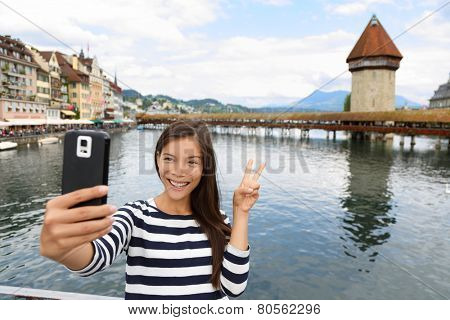 Tourist selfie woman taking self portrait photograph picture with smartphone in Lucerne Switzerland. Travel woman with smart phone by Kapellbr�¼cke Chapel Bridge and Wasserturm water tower, Reuss River